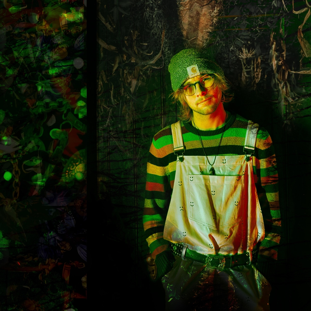 Album art for McCrae's single Garden. It features the artist in low lighting with a dark green background wearing a striped sweater, overalls with emoticons on them, a beanie, a necklace