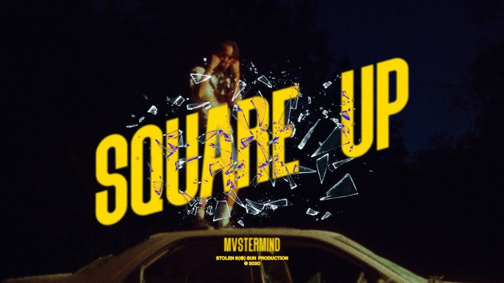 """Cover art for Mvstermind's """"Square Up"""" music video. Features bold yellow text that reads the title of the song and the artist with decorative broken glass. Behind the text, the artist has his fists up near his face and is standing on top of a car"""